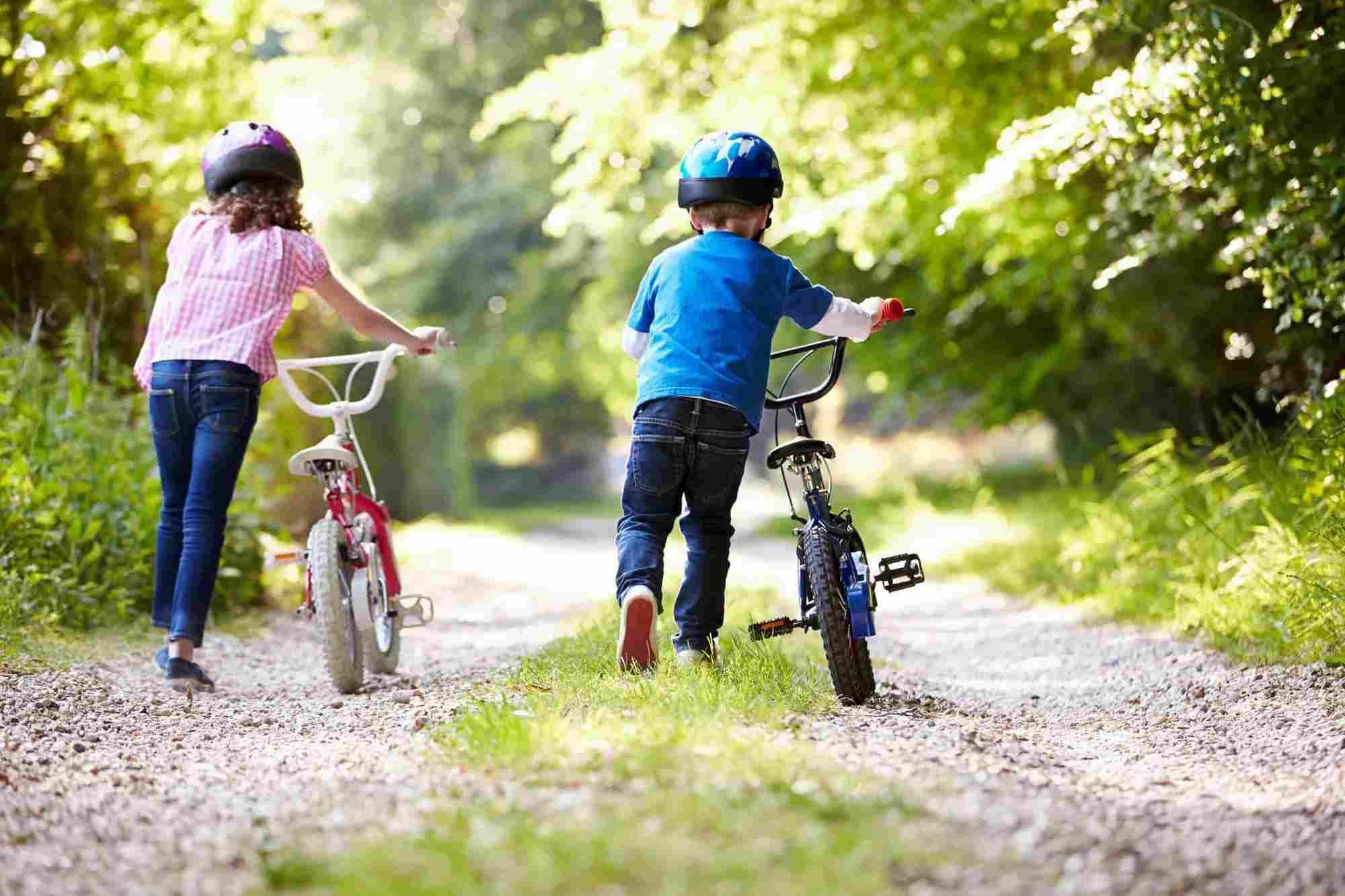 children in helmets pushing bikes along a path