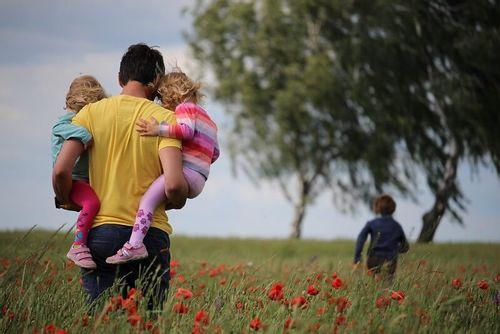 Dad walking holding his children